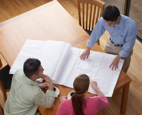 High angle view of an architect showing blueprints to a young couple --- Image by © Royalty-Free/Corbis